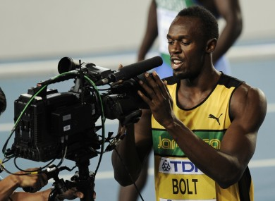Usain Bolt celebrates into the camera after winning his 100m heat.