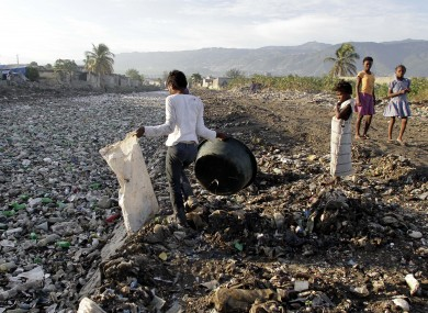 A woman looks for plastic bottles floating in a canal in the Cite Soleil slum of Port-au-Prince on Sunday 31 July 2011