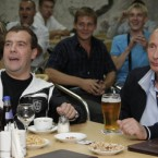 Russia's president and prime minister watch Russia play Argentina in a friendly soccer match on TV in a café on 12 August, 2009. (Dmitry Astakhov/AP/Press Association Images)