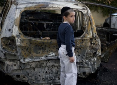 A boy stands next to a burned cars following Saturday night's rocket attacks from the Gaza Strip, in Ashdod, southern Israel
