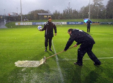 Referee Neil Doyle takes a look at the playing surface in Belfield earlier this evening.