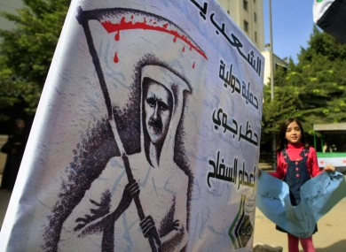 A Syrian girl flashes anti-Syrian regime slogans in front of an anti-Bashar poster outside the Arab League headquarters in Cairo, Egypt,