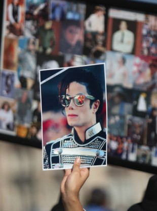 File photo: A fan holds a photograph of the late Michael Jackson.