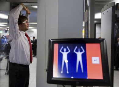 A Schiphol Airport employee demonstrates a body scanner in December 2009.