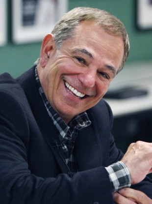 ESPN analyst Bobby Valentine smiling as he answers questions from reporters following his interview for the vacant Boston Red Sox manager position.