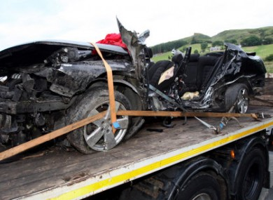 The black Volkswagon Passat, in which seven friends were killed, is removed from the scene in Donegal of the worst road accident on record.