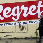 22 November 2010: A woman passes graffiti in Dublin Monday (AP Photo/Peter Morrison)