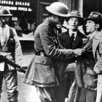 An Irish civilian adopts a defiant stance as a British soldier searches him on the street in the run-up to the War of Independence. Image: Kilmainham Gaol Museum