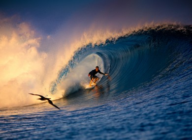 A surfer catches a wave off Tavarua Island, Fiji.