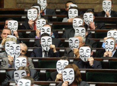 Lawmakers from the leftist Palikot's Movement cover their faces with masks as they protest against ACTA