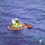 The three astronauts inside their landing pod after returning through the Earth's atmosphere. Members of the US Navy are alongside in a raft. (NASA)