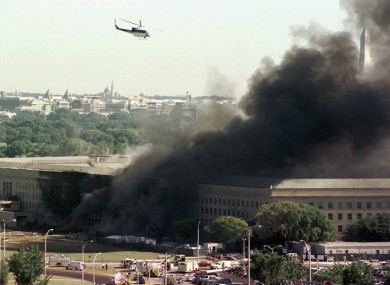 A helicopter flies over the burning Pentagon on 11 September 2001.