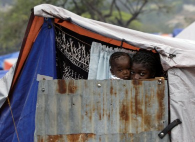 A woman and child peer from their emergency housing at the Petionville Golf Club in Haiti, two months after the 2010 quake.