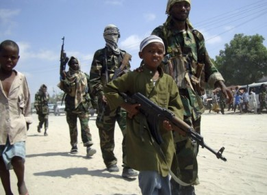 Jan 2010: A young boy leads a group of al-Shabab fighters in Mogadishu's Suqaholaha neighbourhood.