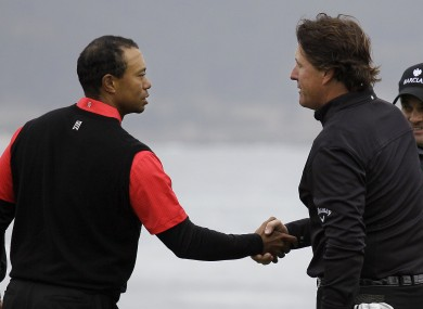 Tiger Woods, left, shakes hands with Phil MIckelson on the 18th green.