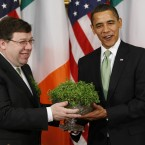 On his first St Patrick's Day in office, President Barack Obama receives shamrock from Taoiseach Brian Cowen at the White House. (AP Photo/Gerald Herbert/PA Images)