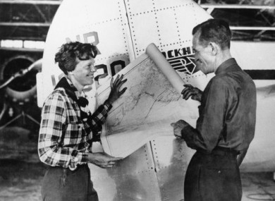 1937: Amelia Earhart and Fred Noonan pose with a map of the Pacific showing route of their last flight.