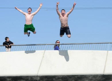 Michael Spain and Joseph McCarthy jump into the Liffey in Dublin's city centre on Wednesday as temperatures rose to 19 degrees