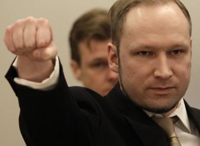 Breivik gestures as he arrives at the courtroom.
