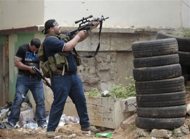 A Sunni gunman fires during a clashes in the northern port city of Tripoli, Lebanon today.