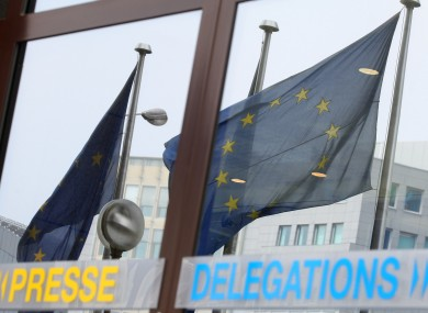EU flags wave as they are mirrored at the European Council building in Brussels