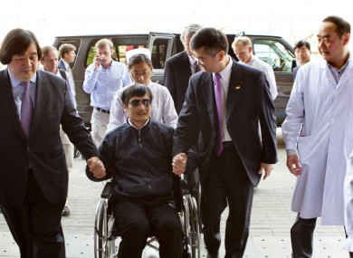 Guangcheng is wheeled into a hospital by US Ambassador to China Gary Locke yesterday.
