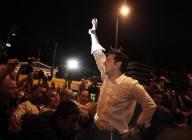 Left Coalition party leader Alexis Tsipras waves to supporters in central Athens after elections on Sunday, May 6, 2012