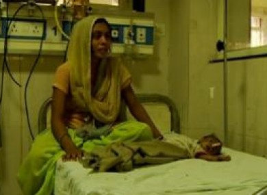 Baby Radhika recovering in hospital beside her mother.