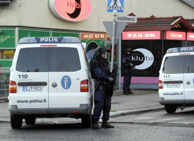 Police officers guard the area in Hyvinkaa, Finland, where a gunman has killed one person and wounded eight others in what appeared to be a random shooting
