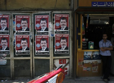 A worker stands in front of his shop next to posters with pictures of presidential candidate Mohammed Morsi