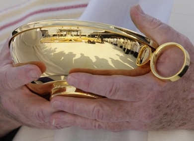 A priest holds a bowl of communion wafers