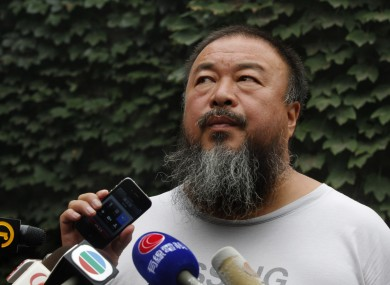 Dissident artist Ai Weiwei listens as his lawyer announces over a speakerphone the verdict of Ai's lawsuit against the Beijing tax authorities in Beijing Friday, July 20, 2012