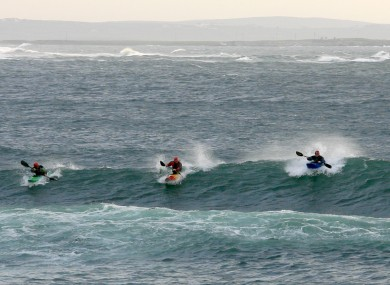 Kayakers ride a large wave at the popular surf beach of Spanish Point, County Clare - now reopen for business.