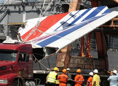 Workers unloading debris, belonging to crashed Air France flight AF447, from the Brazilian Navy's Constitution Frigate