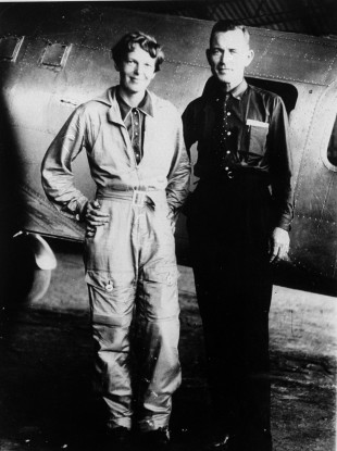 Amelia Earhart and her navigator Fred Noonan posing in front of their Lockheed Electra in May 1937.