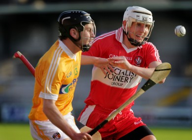 Derry's Ciaran McIntyre in action with Antrim's Stephen Smith.