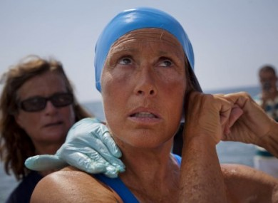 Diana Nyad preparing her hat for the swim as a team member helps apply a protective ointment on her skin.