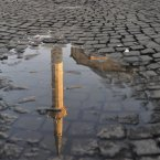 The minaret of the Grand Mosque is reflected in a puddle of water on a cobblestone road in Kosovo's capital Pristina. (AP Photo/Visar Kryeziu/PA)