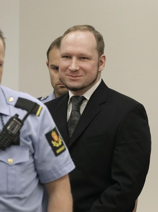 Anders Behring Breivik smiles as he arrives in the courtroom to hear its verdict earlier today.