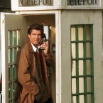 Photo Photocall Ireland  Oops, a hunk in a box. Could you exchange that for a book? Doubt it.  Irish actor Pierce Brosnan in a old wodden style telephone Kiosk on the set of