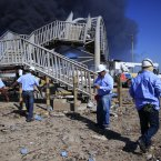 Rescue workers stand in front of a pedestrian bridge damaged by the refinery blast. (AP Photo/Ariana Cubillos/PA)