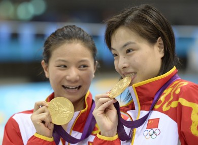 Gold medalists He Zi, left, and Wu Minxia, right, pose with their medals after the 3 Meter Synchronized Springboard final.