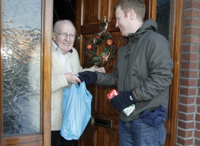 John Sherwin from the Dublin City charity, Care Local, visits 87-year-old Joe Reddin to deliver groceries.
