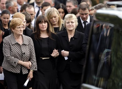 Essie Spence (right) wife of Noel and the mother of Graham and Nevin Spence, with Graham's wife Andrea (centre) walking behind the three coffins.