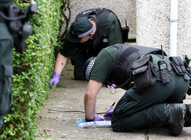 Police officers search a garden where drugs were found during a series of drug raids in the Lurgan area of Northern Ireland.