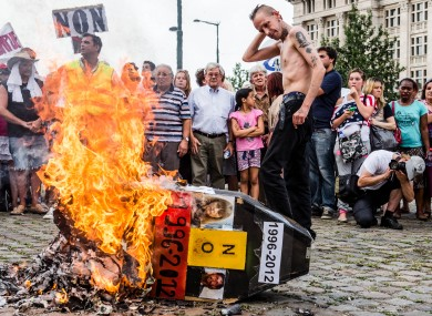 Demonstrators gather around a burning mock coffin with the pictures Marc Dutroux and Michelle Martin during a march to remember their victims, Brussels, August 2012.