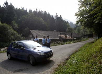 A gendarme blocks access to site where people were shot to death near Chevaline.