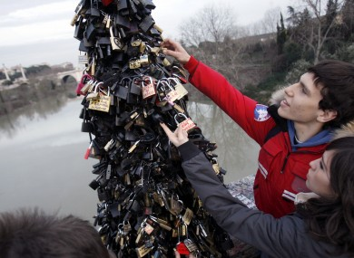Youths read messages on locks attached to a lamp post on Rome's Ponte Milvio Bridge, on Valentine's Day, Wednesday, Feb. 14, 2007