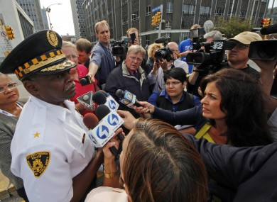 Pittsburgh Police Chief Nate Harper, third from left, briefs media outside the 3 Gateway Center building, rear center, in downtown Pittsburgh