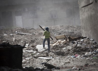 A Free Syrian Army fighter holds a rocket-propelled grenade launcher while taking cover after a tank blast in Aleppo, Syria.